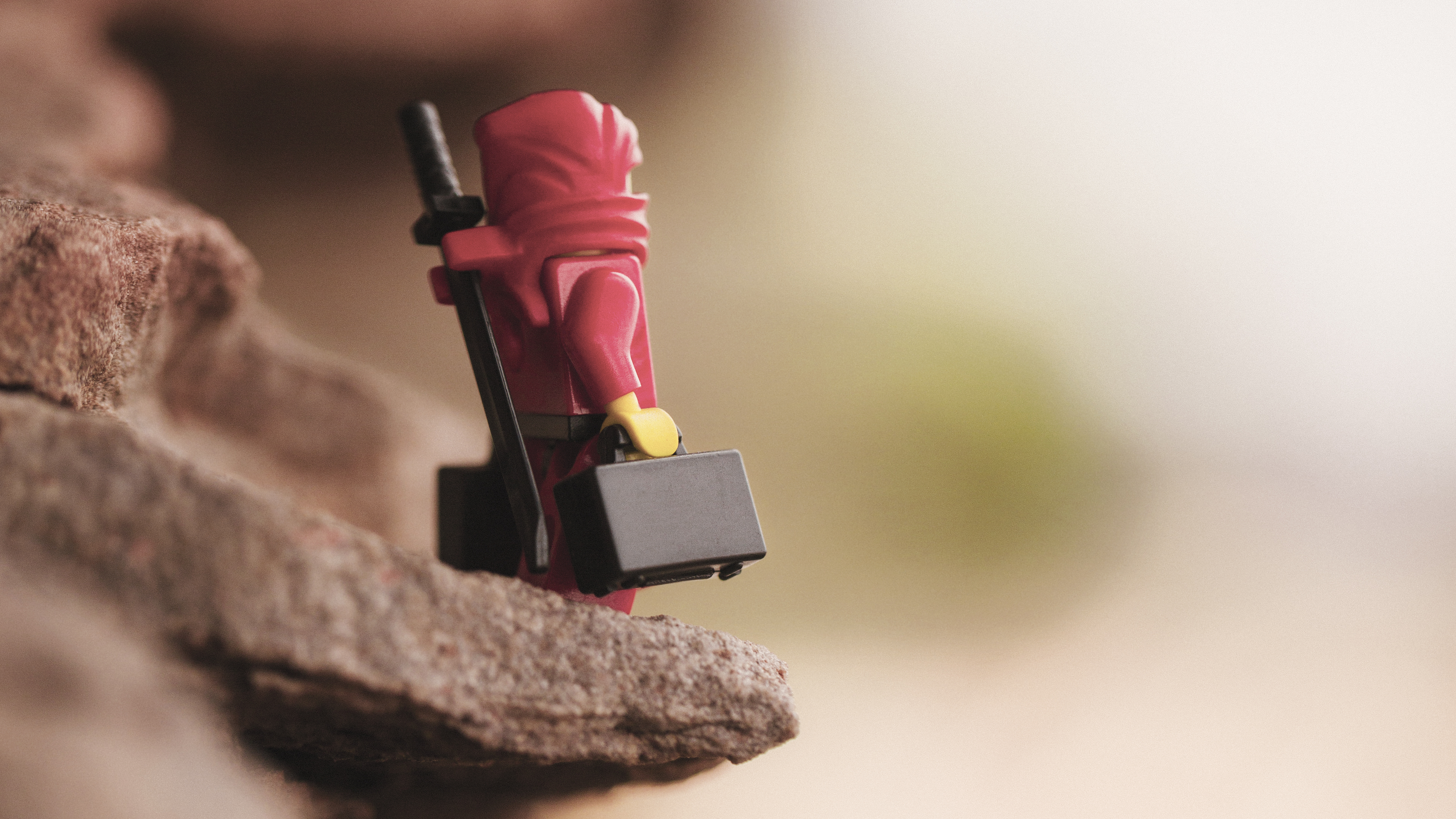 A Lego Ninja stands on the edge of a cliff holding two suitcases wondering where he should go.