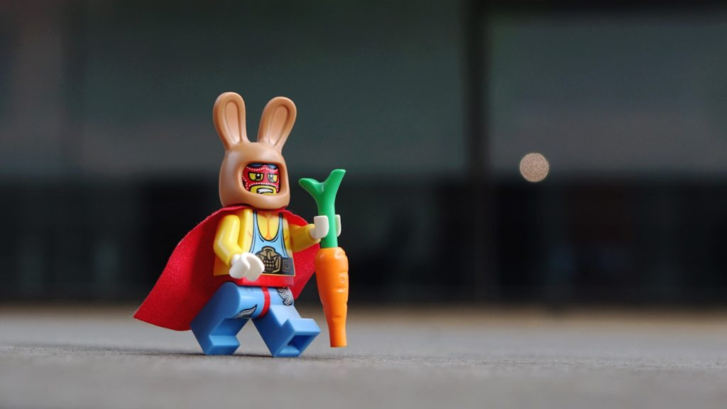 a lego wrestler in a bunny mask running with a carrot