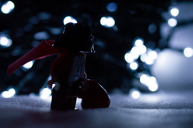 Darth Santa delivering Christmas presents in front of lit tree