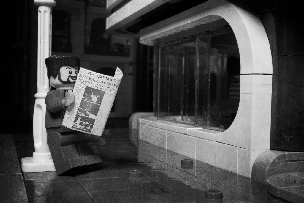 Reading a newspaper under a street lamp