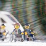 three lego men in wheelchairs in front of an oncoming train taken with a lensbaby by shelly corbett