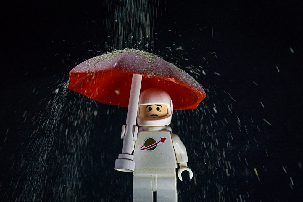 Spaceman under an umbrella, getting covered in dust, which is a distraction.