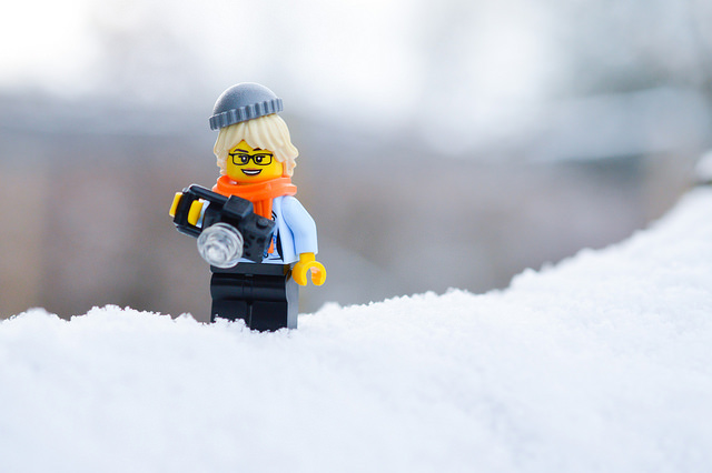 LEGO minifigure holding a camera in the snow