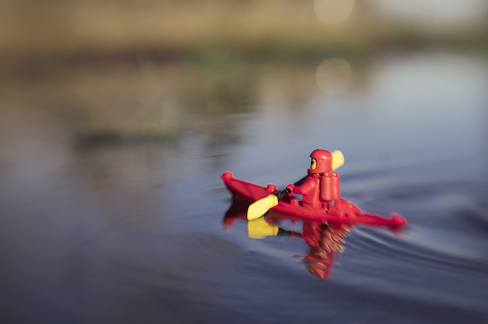 red classic lego spaceman kayaks across the still pond taken with a lensbaby by shelly corbett