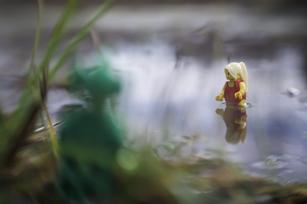A blurry LEGO swamp monster hides in the bushes and watches the bathing beauty in the lake - taken with a LensBaby by Shelly Corbett