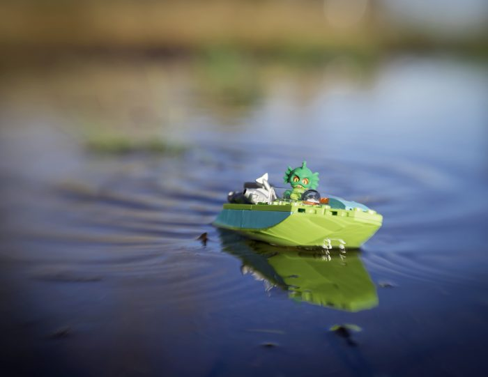 Lego Swamp Monster drives a green power boat across the blue lake by Shelly Corbett