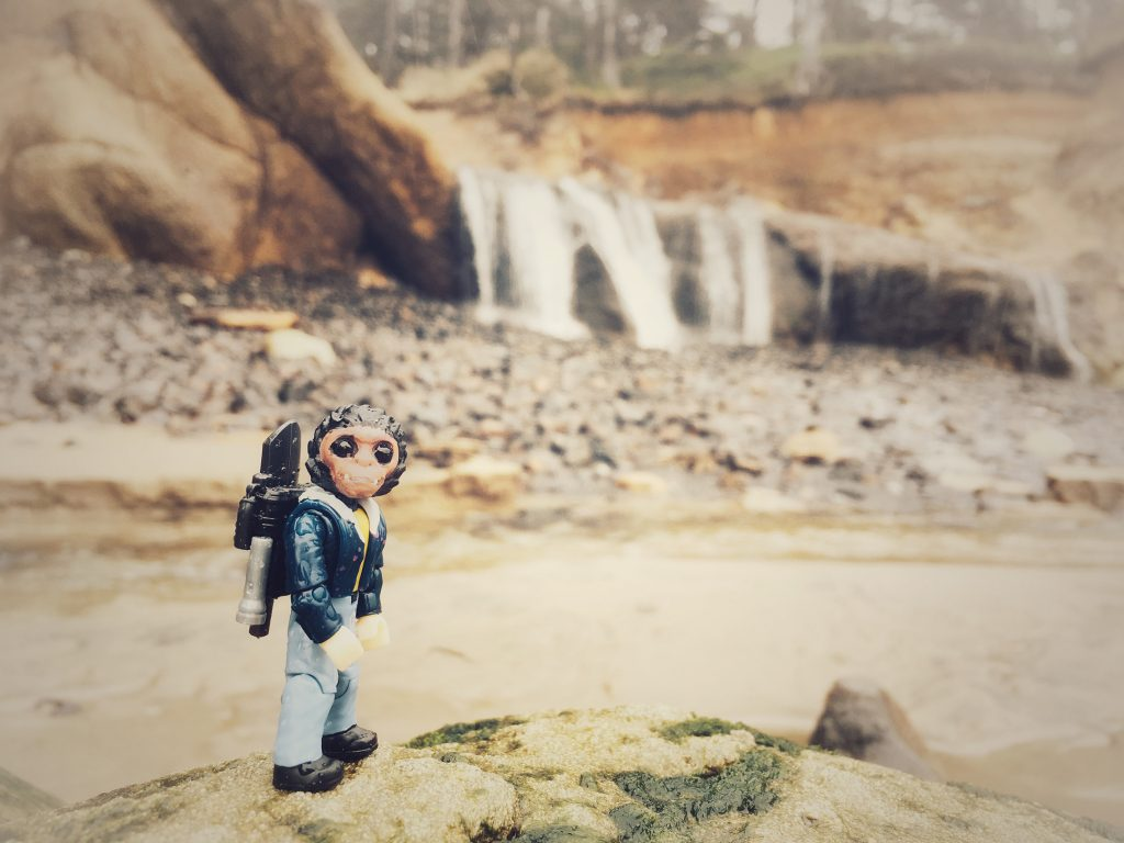 toy monkey looks at camera with waterfall in background