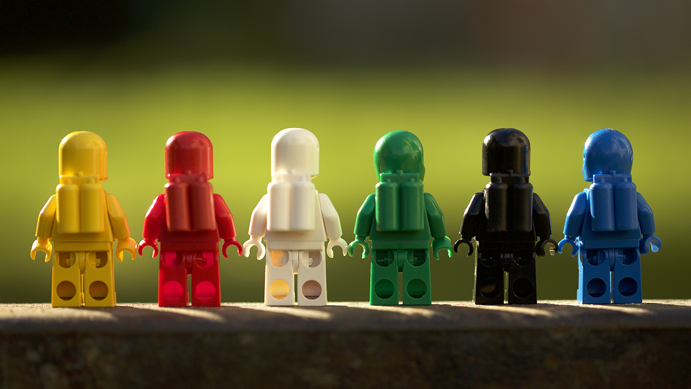 Six classic LEGO spacemen are lined up in a row facing away from the viewer. All six colors of the spacemen are represented in this outdoor toy photograph.