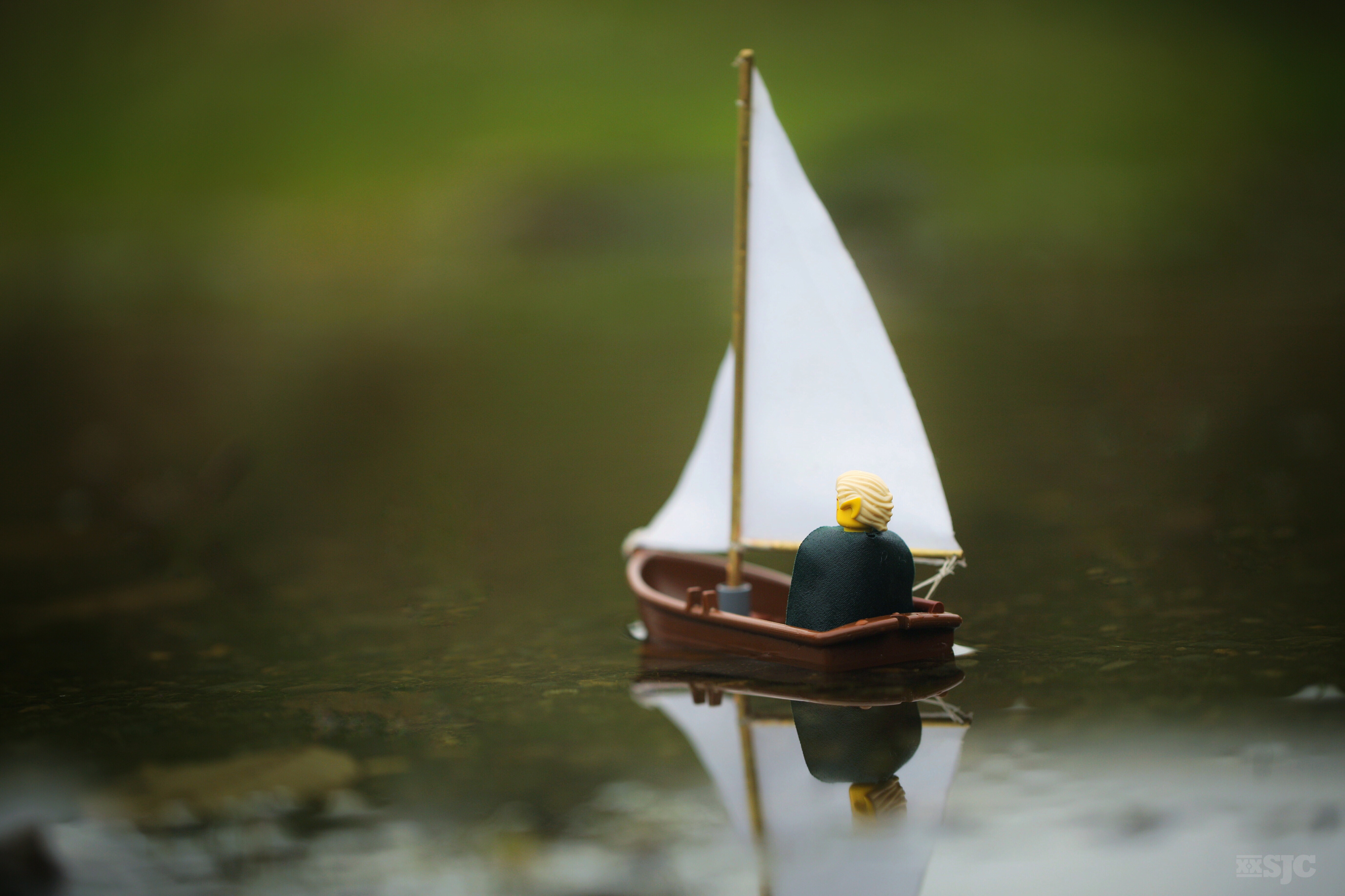 Lego Legolas sits in the back of a lego sailboat and sails away in a small puddle to parts unknown.