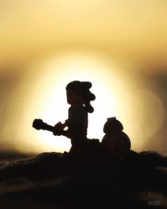A lego Rey and BB8 walk across the sand with the setting sun leaving them in full relief.