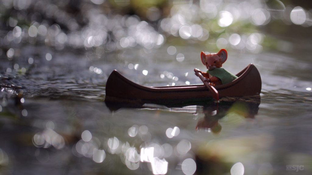 A lego version of the Mouse Guard character Lieam journeys down the sparkling river in his Lego canoe.