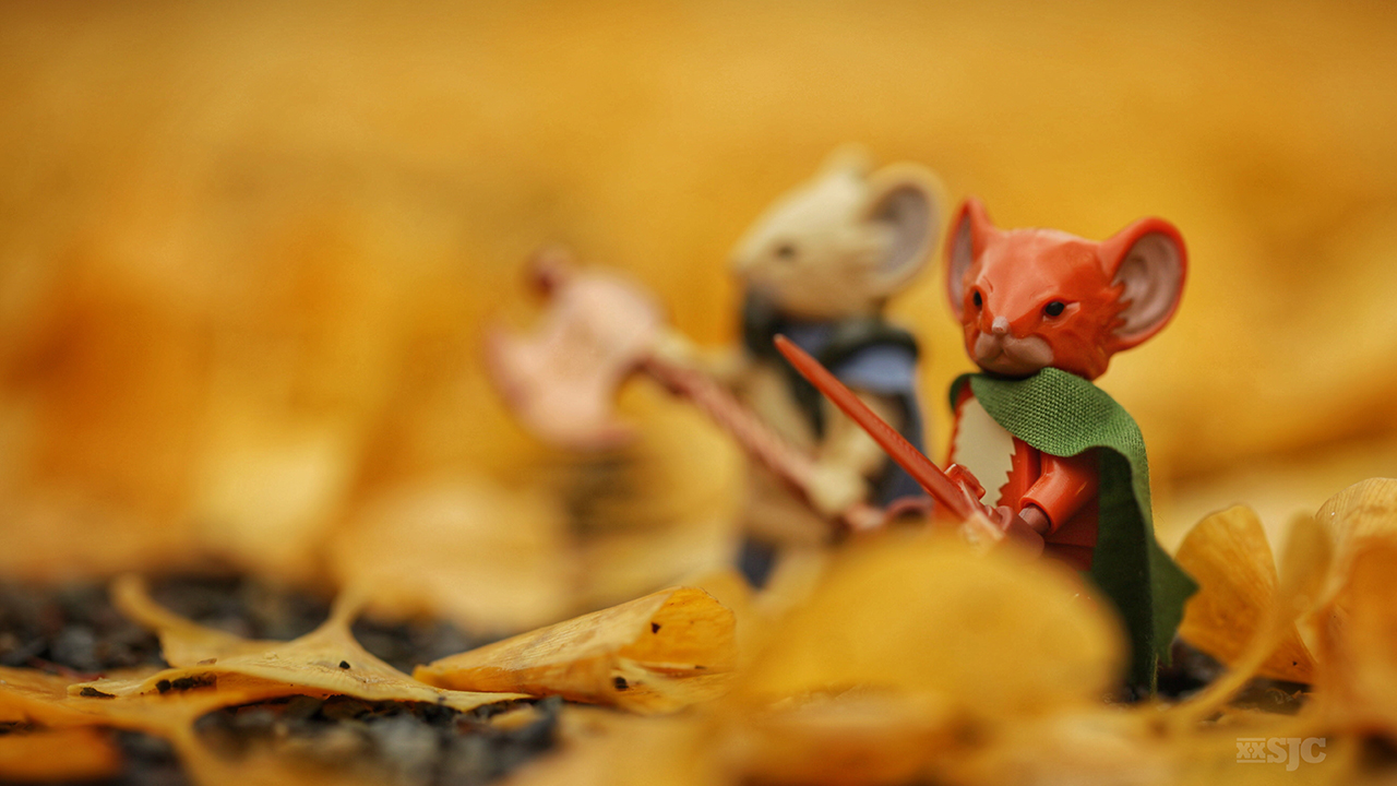 two lego mouse guard figures outfitted with their weapons walk through the fallen leaves as if in a sea of gold. Image by Shelly Corbett