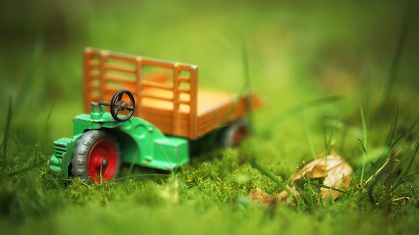 A small red and green child's toy tractor sits in the grass.