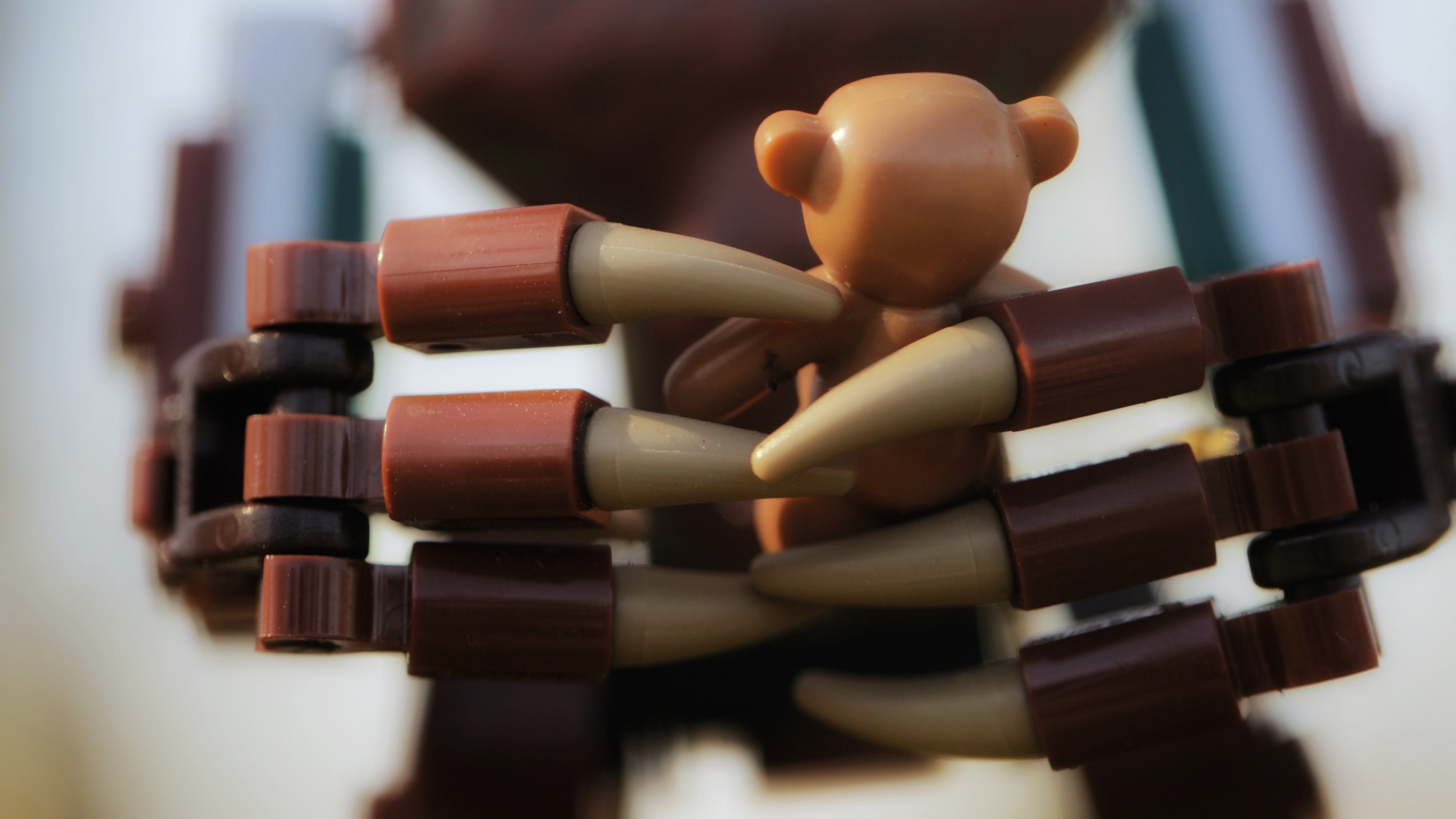The large lego hands of Groot cradle a small lego teddy bear in this close up image.