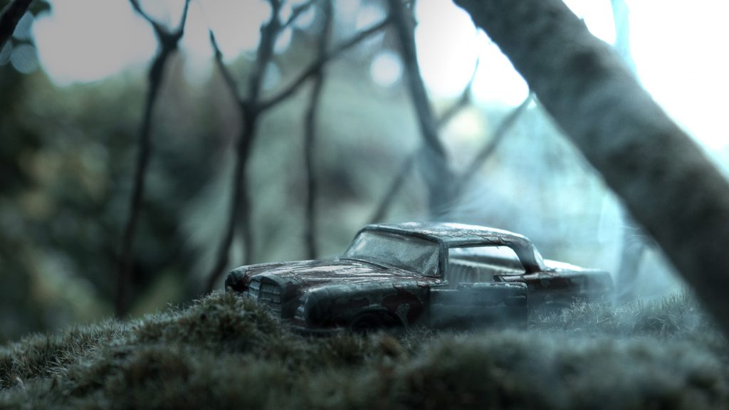 Toy photography of an old car in the woods