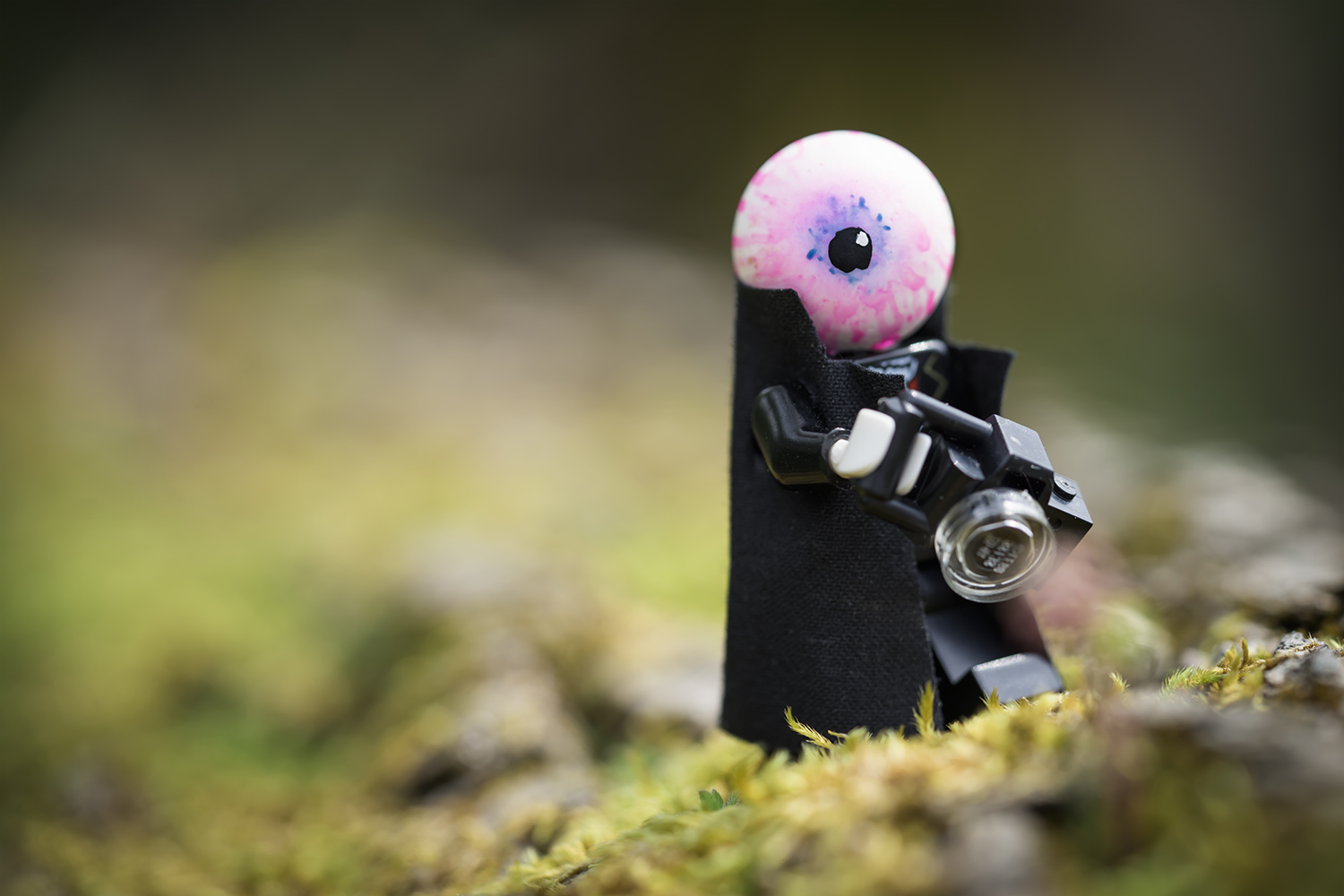Custome LEGO mini figure with eyeball for a head holds a camera. Custom by Dennis Taylor, Photo by Shelly Corbett