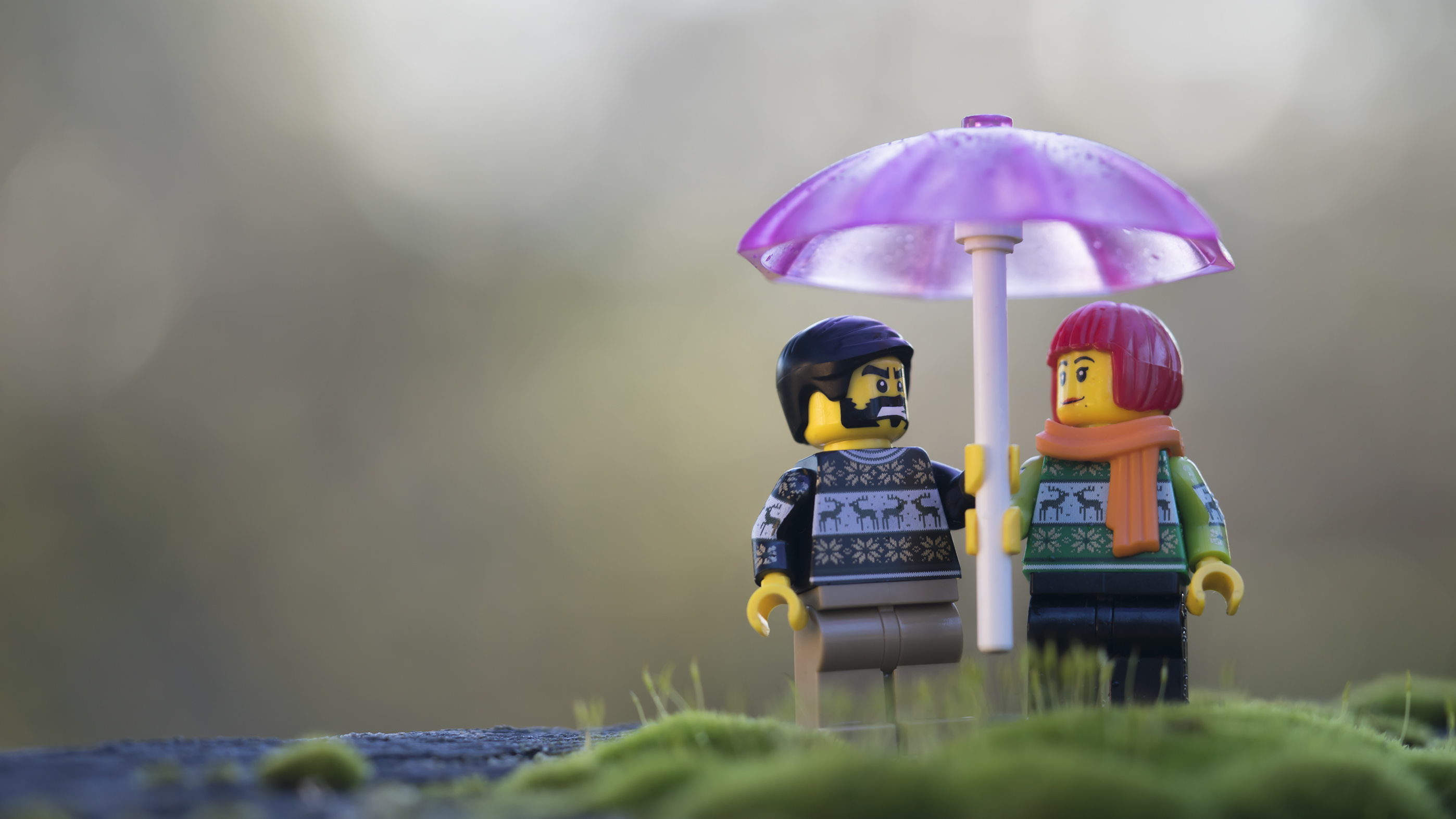 Two LEGO minifigures stand under a pink umbrella in their Christmas sweaters. Photo by Shelly Corbett