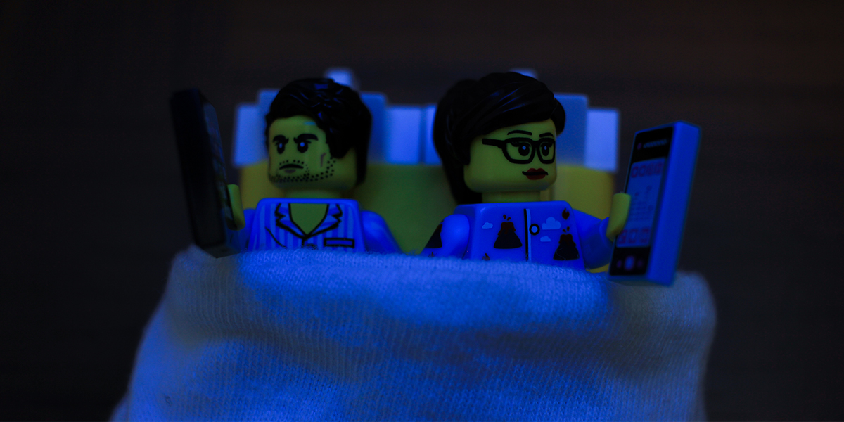 LEGO minifigures in bed on phones together by James Garcia