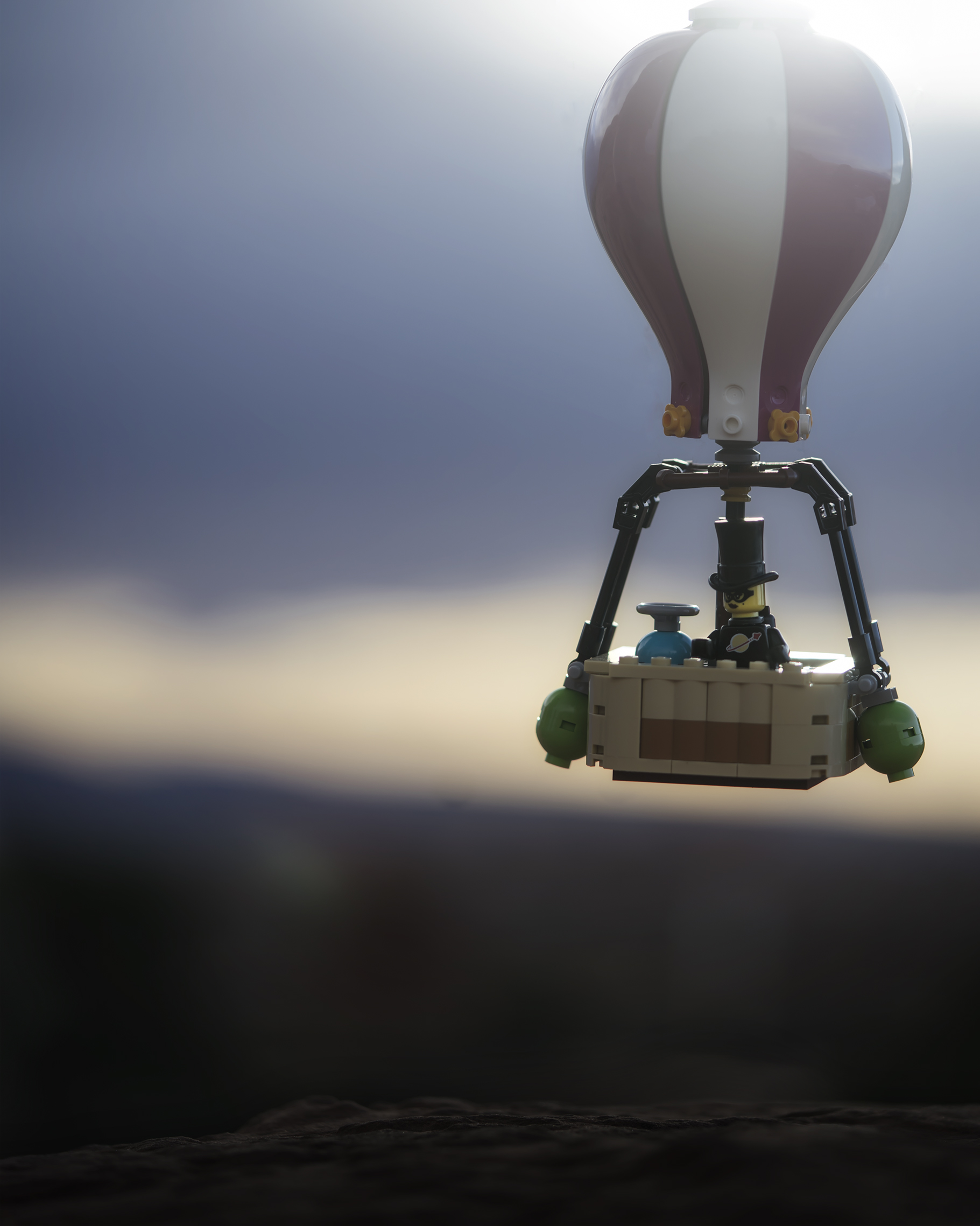 LEGO hot air ballon floats in the air with dark clouds looming in the distance.