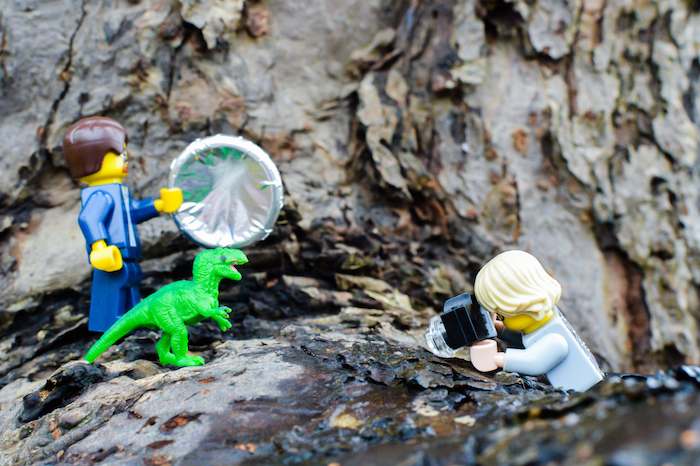 LEGO figures taking photos of toy dinosaur