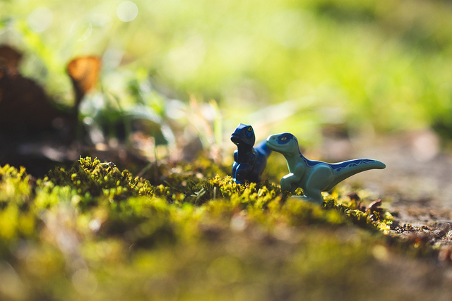 Teeny tiny dinosaurs having a conversation in moss.