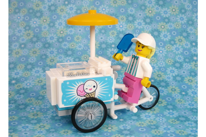 The girl is riding the ice cream bike