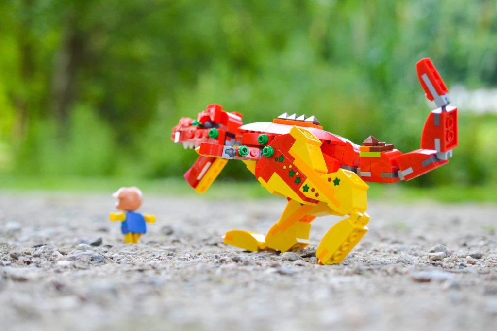 LEGO dinosaur chasing a piggy