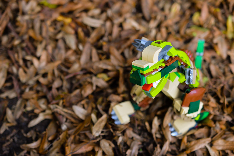 LEGO dinosaur playing in the autumn leaves