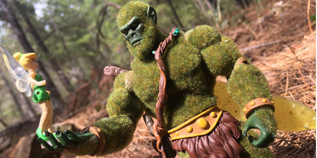 A photo of a fluffy green muscular action figure standing in a pine forest, holding a little toy of Tinkerbell in its outstretched hand.