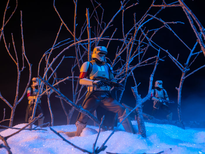 Scarif troopers patrolling through the misty woods in the snow.