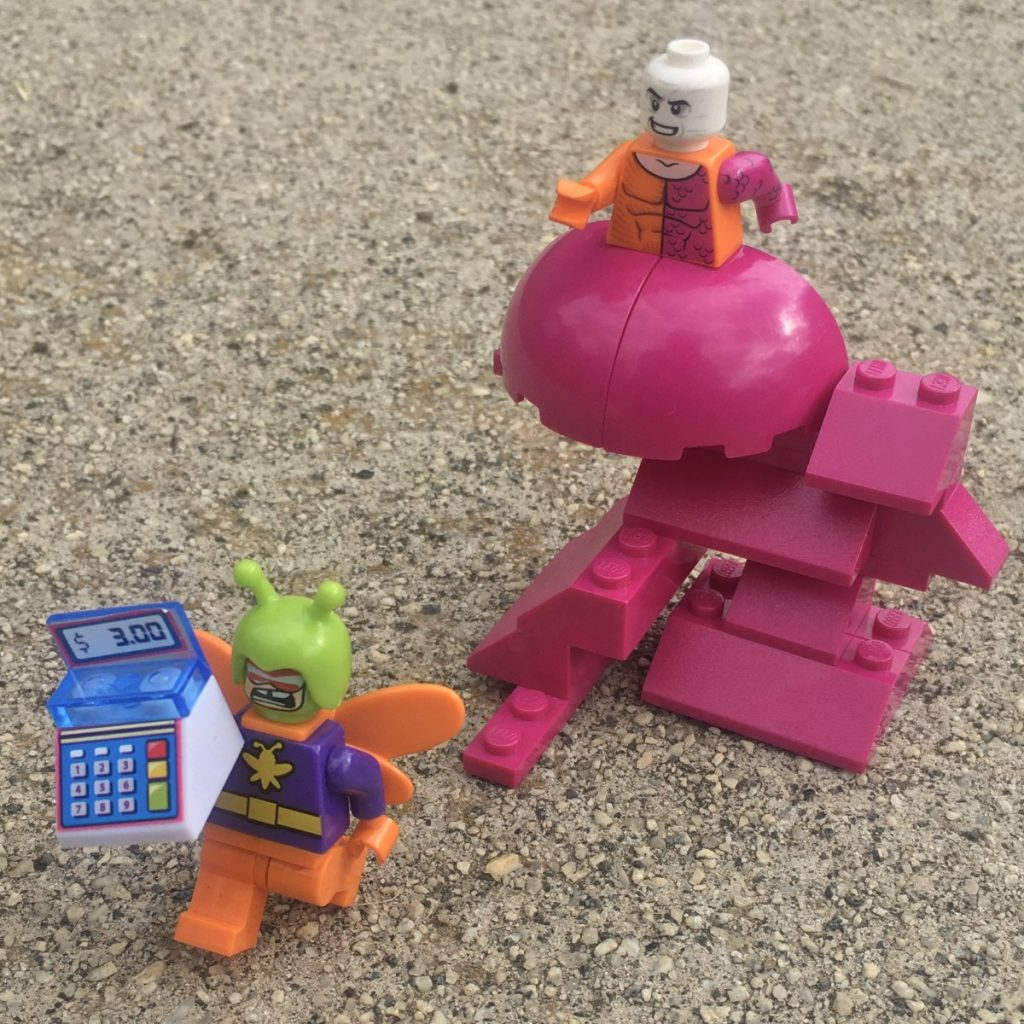 Photo by Adam Ford: Lego minifigure scene: DC comics superhero Metamorpho chasing supervillain Killer Moth, who has stolen an entire cash register.