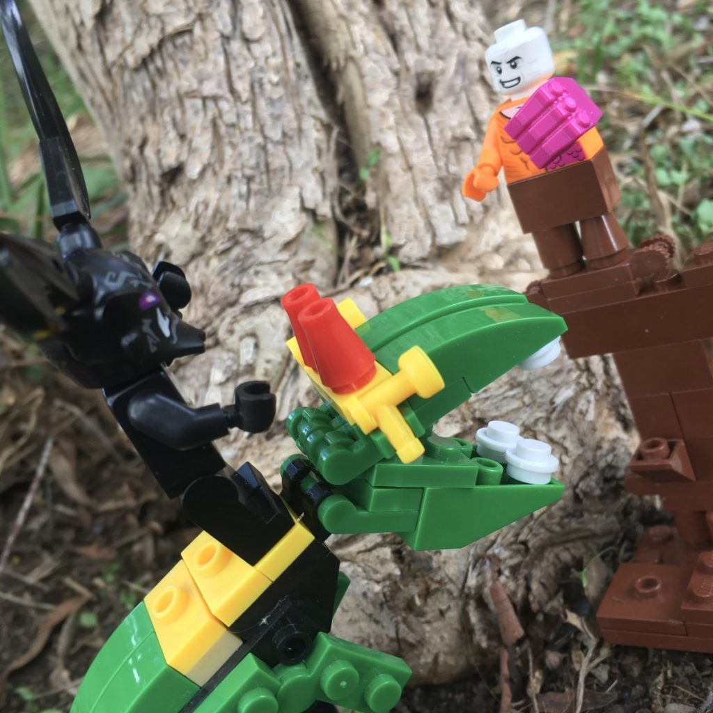 Photo by Adam Ford: A LEGO minifigure scene - DC comics Superhero Metamorpho faces down an Oni Demon mounted on a fierce knockoff dino-beast