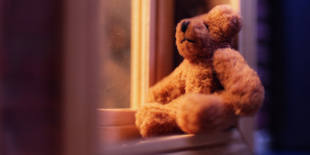 A small brown plush teddy bear sits in the window waiting to be seen by the passing children. Image by Janan Lee