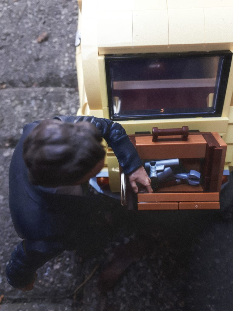 A man looks through a case mounted on the back of the LEGO Fiat 500