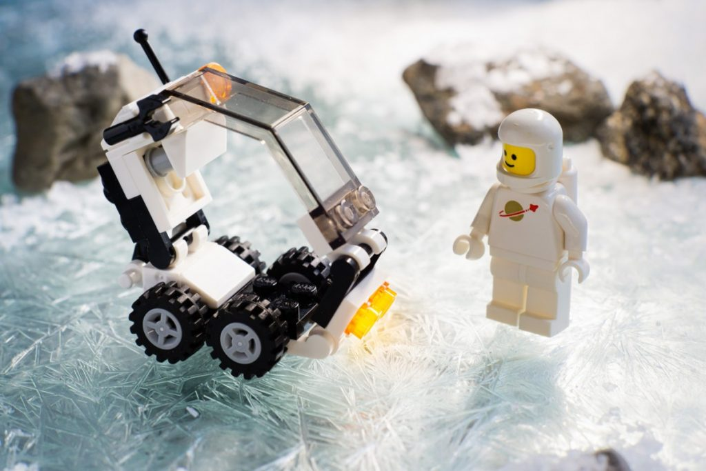 white classic LEGO spaceman stands on a ice surface next two a small brick built transport vehicle. by Anna Bitanga