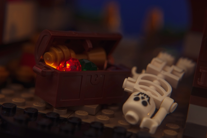 LEGO skeleton lying by the chest filled with treasures