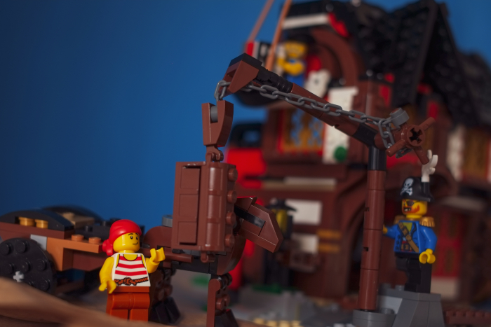 LEGO pirates minifigures lifting the chest from the cart using wooden crane
