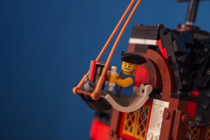 LEGO pirate minifigure playing on accordion while lying in hammock made of sail