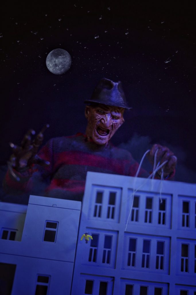 Giant 1:6 scale Freddy Krueger action figure laughing over buildings as person falls by @tromatic_exposure