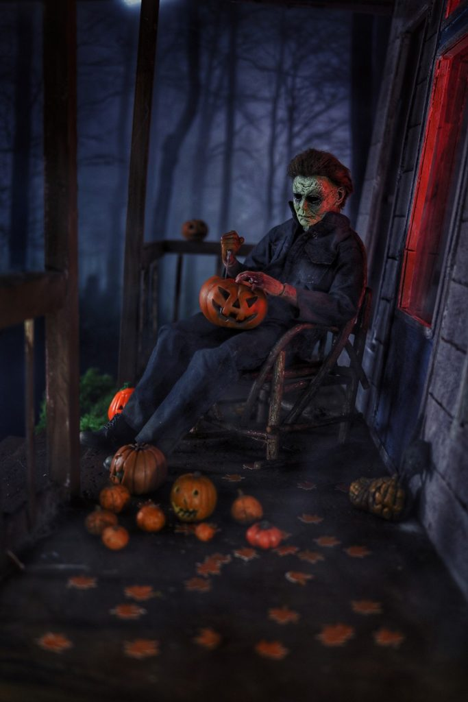 Michael Myers action figure carving pumpkins in rocking chair before Halloween by @tromatic_exposure