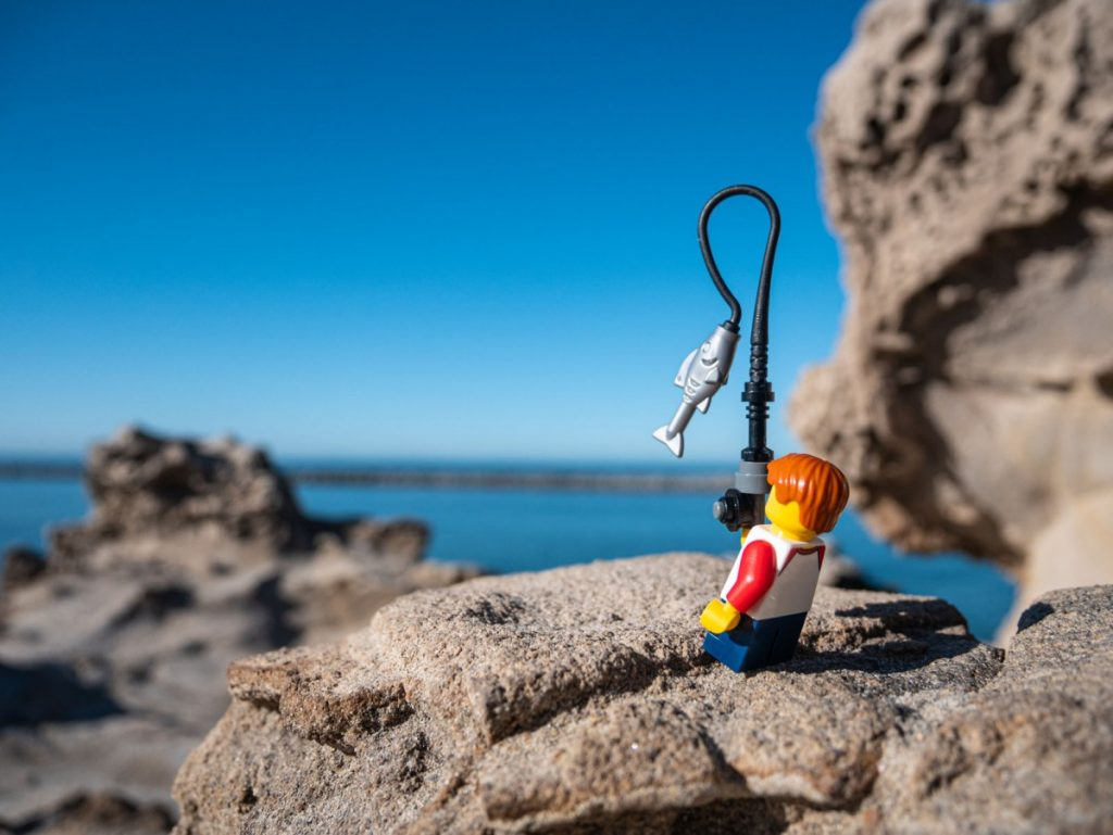 Lego minifig catching fish at the ocean.