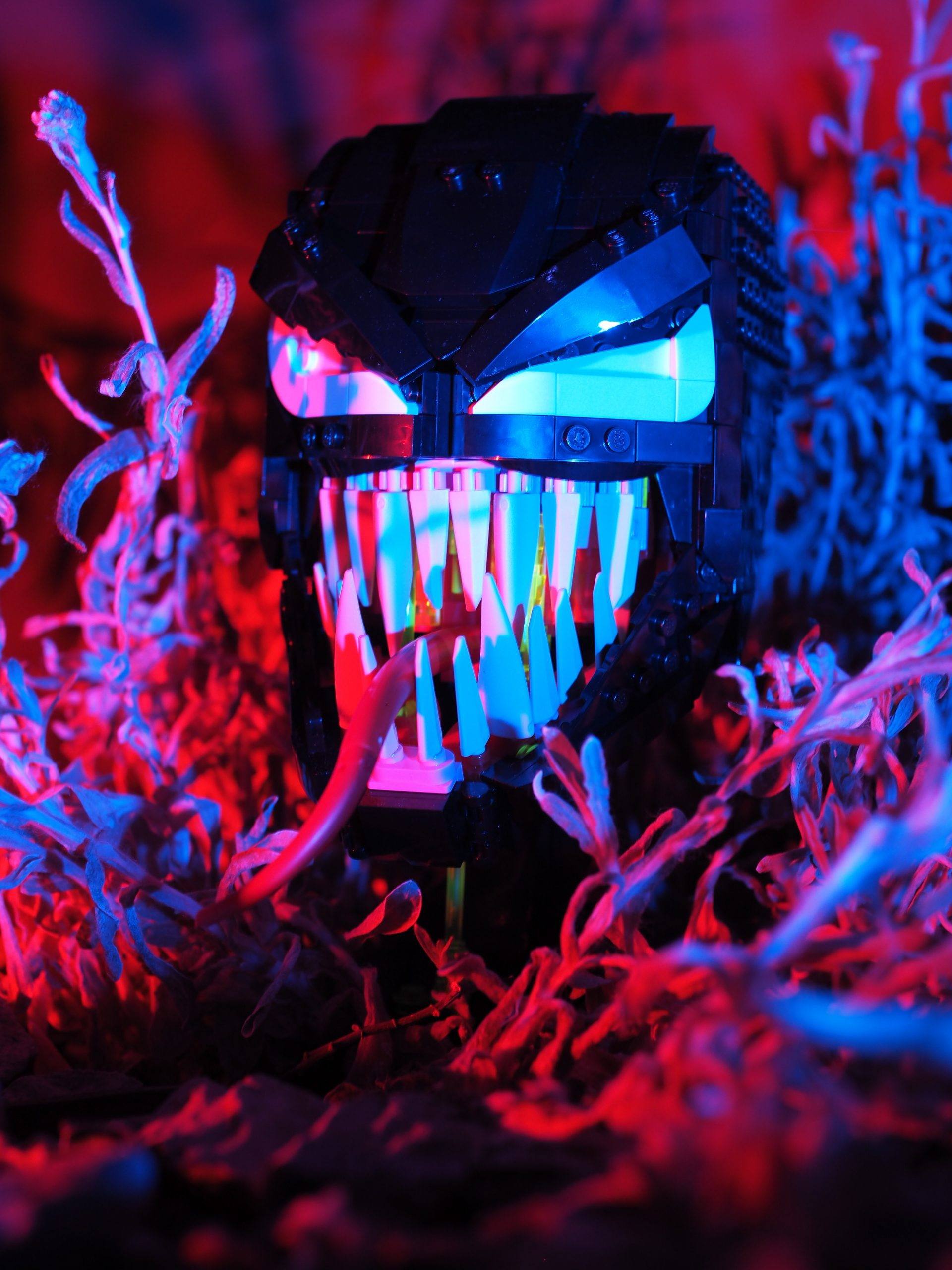 A lego sculpture of Venom in some underbrush with fancy lighting to make it look more scary.
