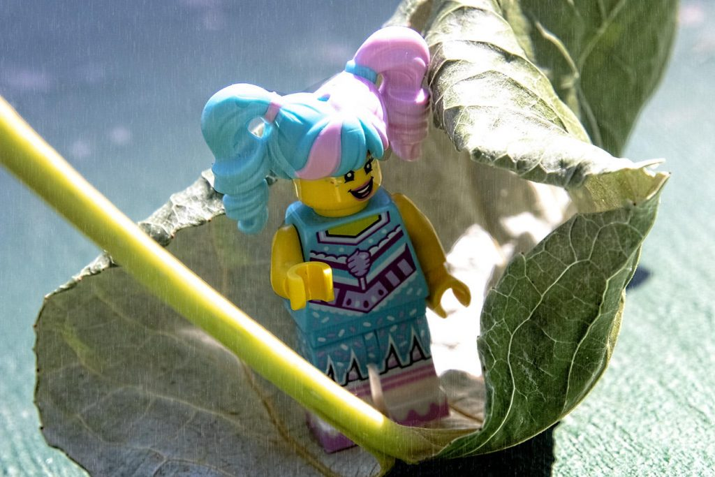 Lego minifigure sliding on the leaf through the rain