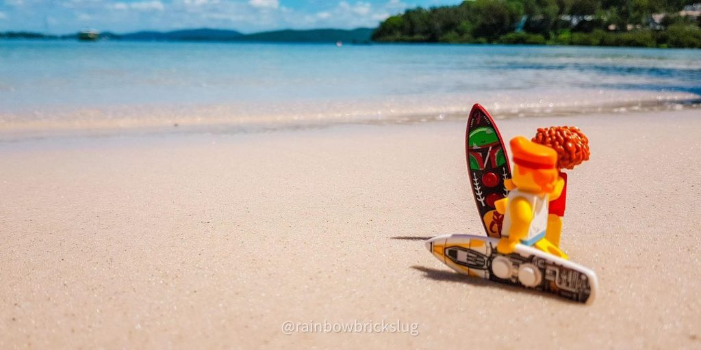 LEGO surfers minifigures with surfboards, standing on the beach