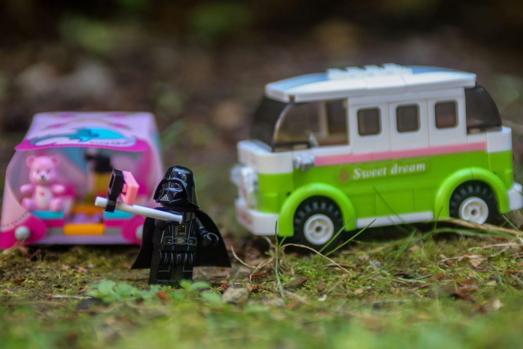 LEGO Darth Vader minifigure taking selfie in front of LEGO Freinds tent and a camper