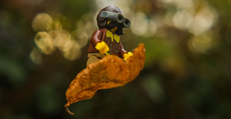 Lego vintage pilot minifigure flyuing on the dry leaf